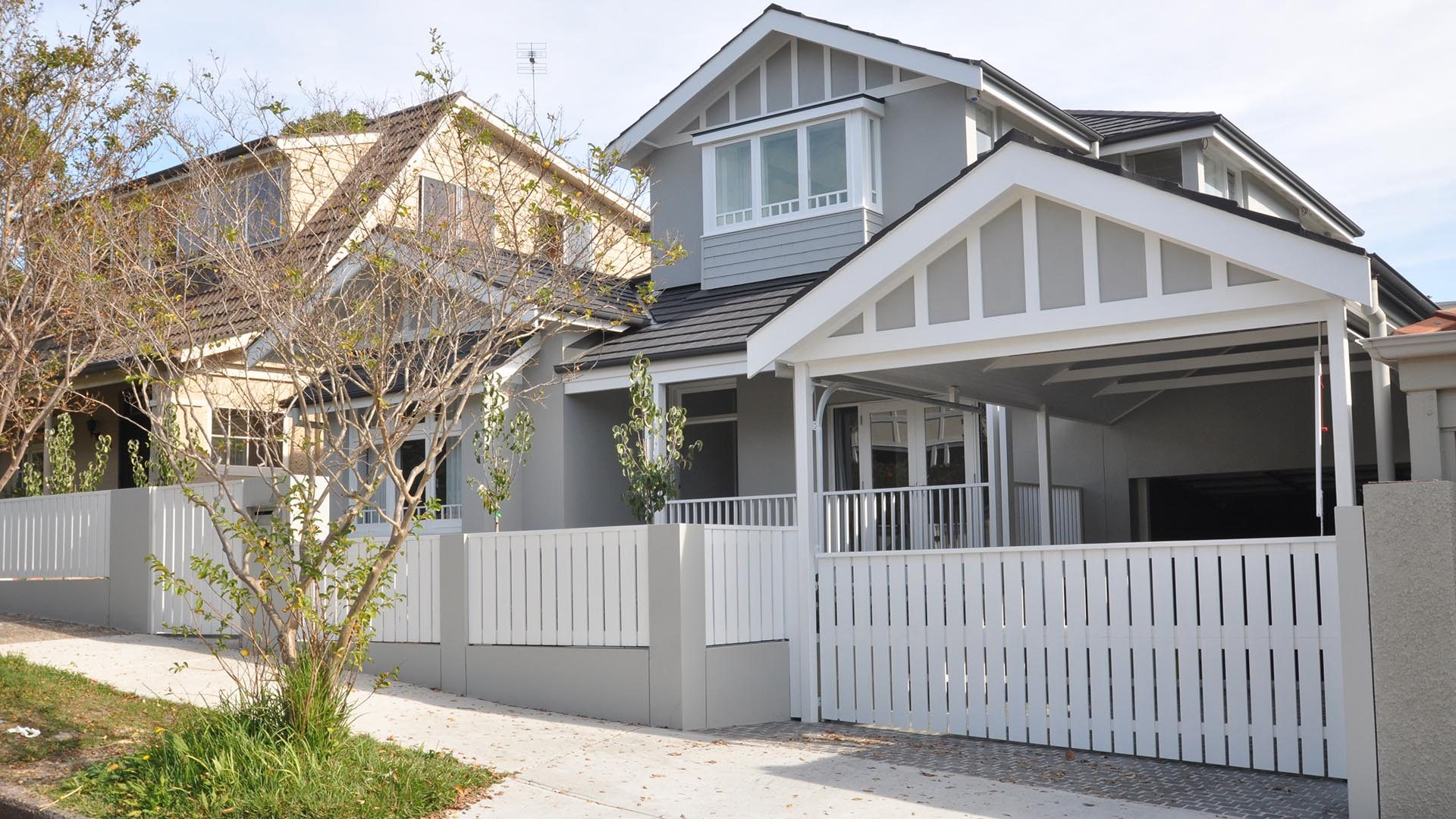 Mosman Front of house with garage and white fence.