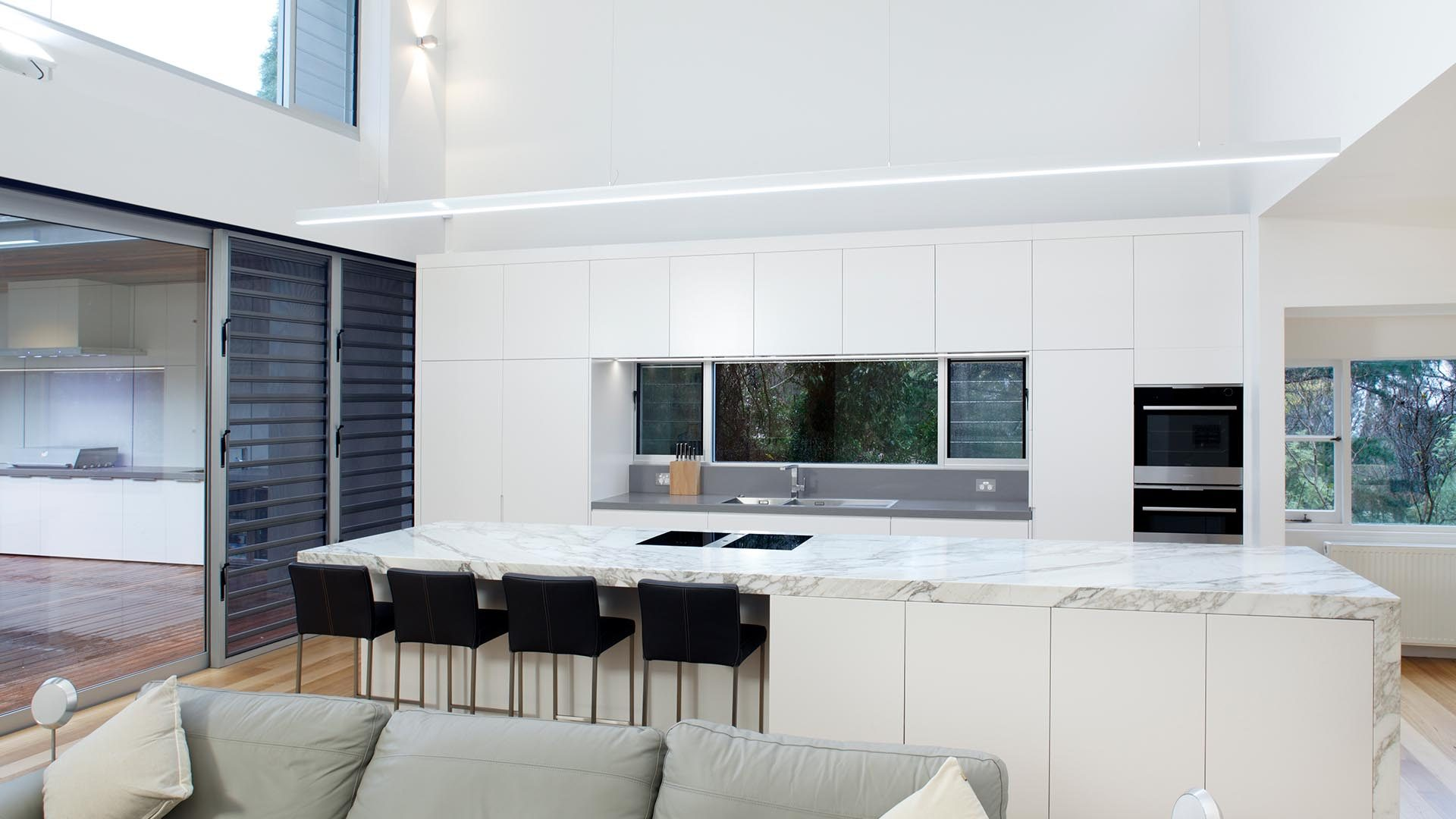 Mittagong Kitchen with floorboards, large stone benchtop and preparation area and bar style seating.